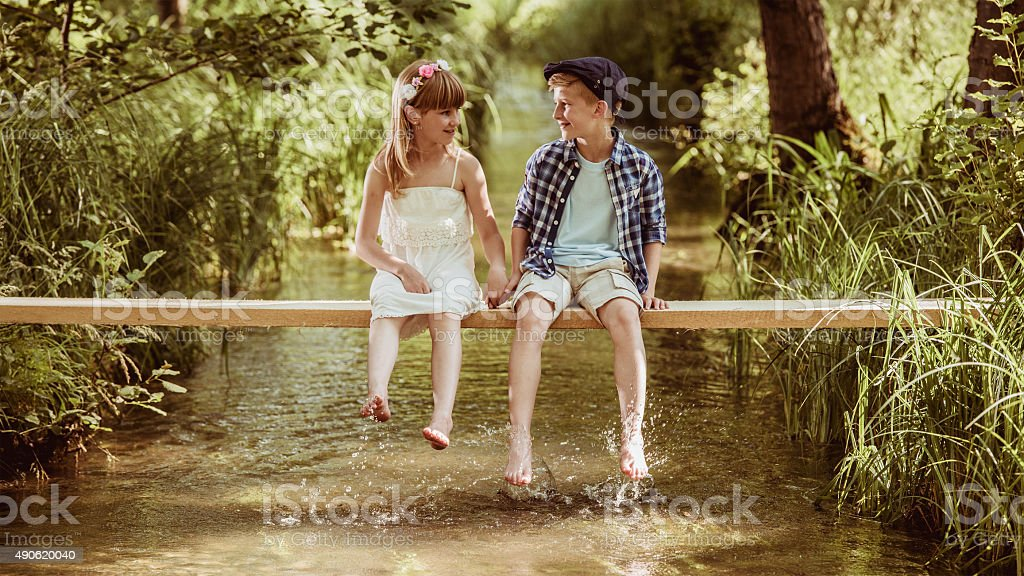 Girl and boy sitting above stream talking and holding hands stock photo