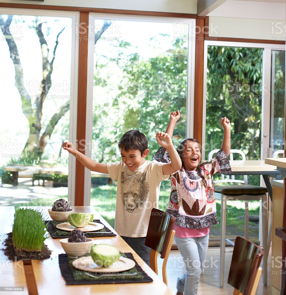 Girl and boy (6-11) standing by dinning table, cheering royalty-free stock photo