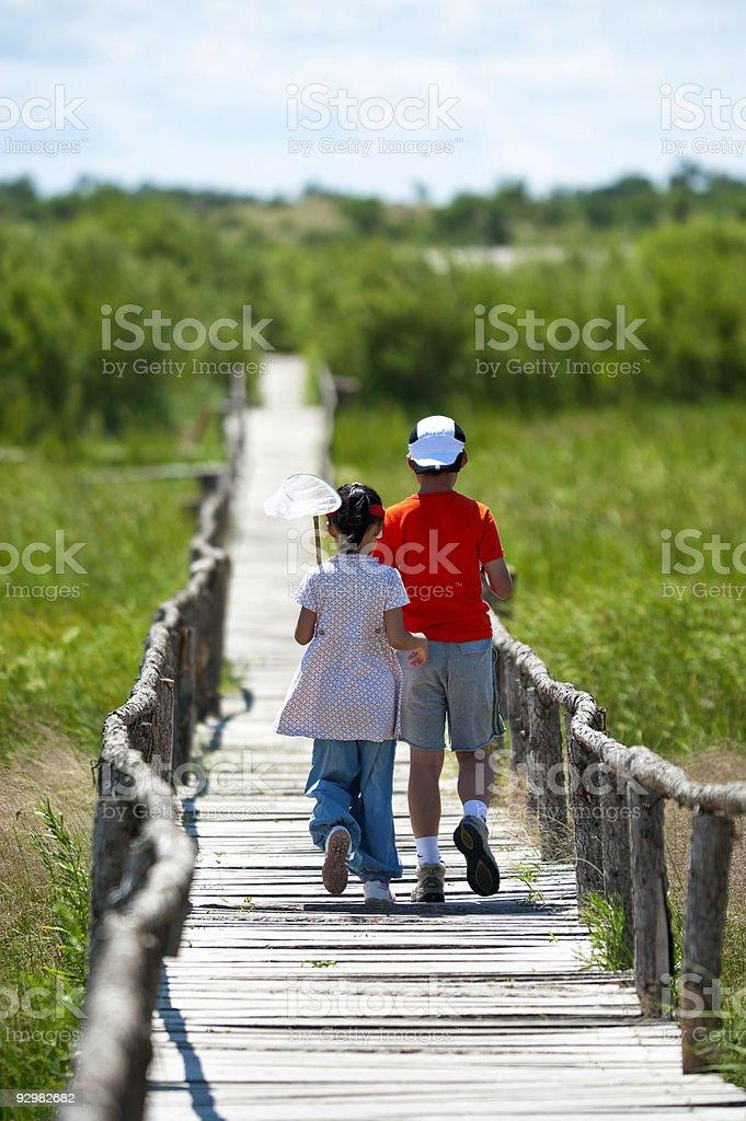 Girl and boy walking on bridge above marshes stock photo