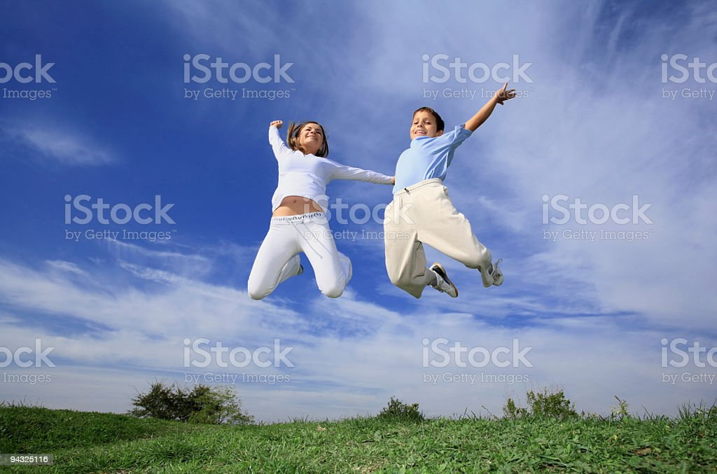 Girl and child jumping in meadow royalty-free stock photo