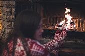 Girl and Christmas socks next to fireplace