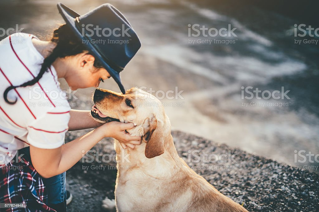 Girl and dog cuddling stock photo