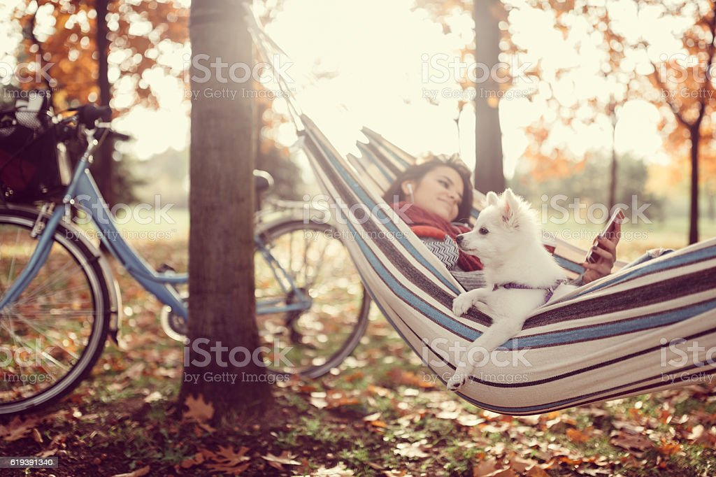 Girl and dog relaxing in hammock stock photo
