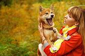 Girl and dog Shiba Inu in autumn park.