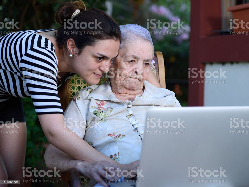 girl and grandma with laptop stock photo