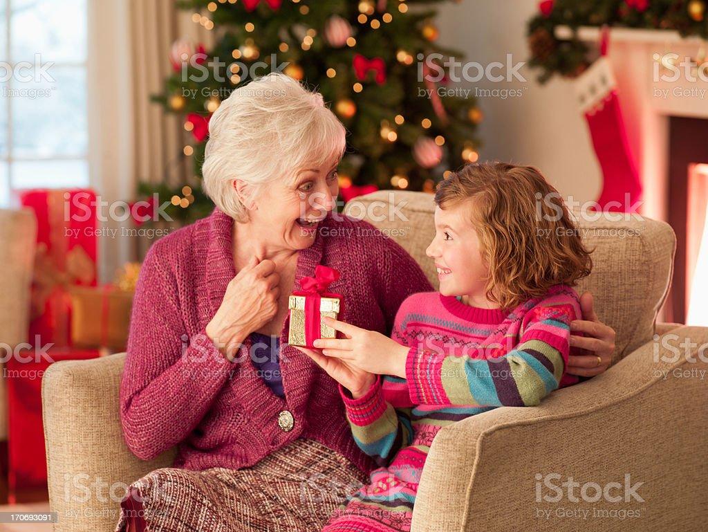 Girl and grandmother holding Christmas gift royalty-free stock photo