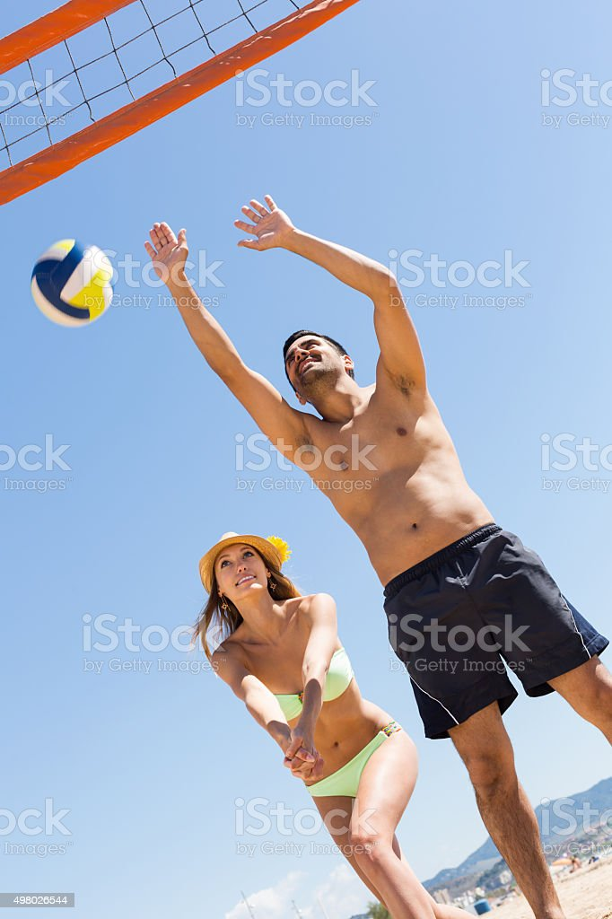 Girl and guy playing volleyball at beach stock photo