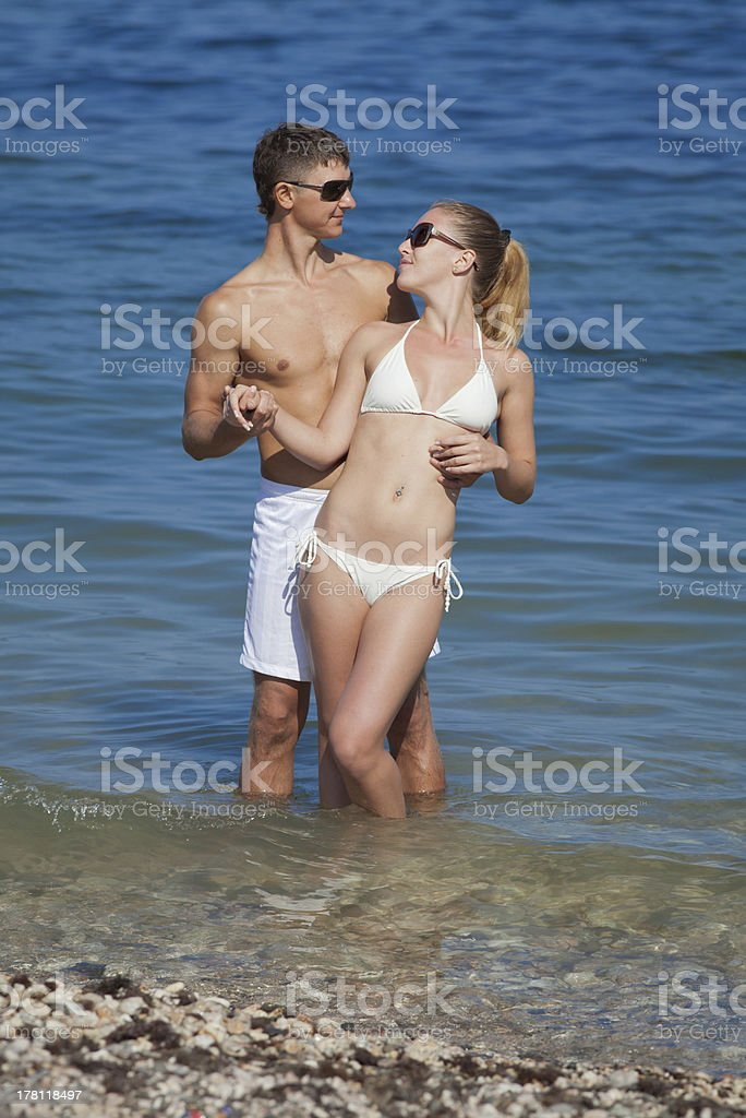 Girl and guy posing in sea stock photo