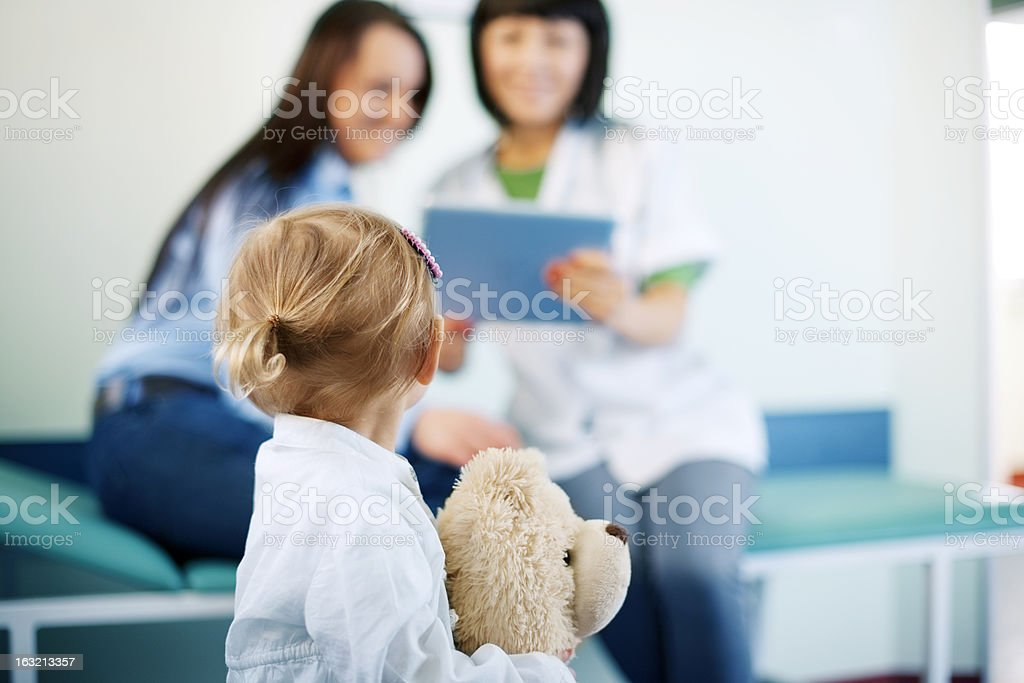 Girl and her bear waiting to see the doctor royalty-free stock photo