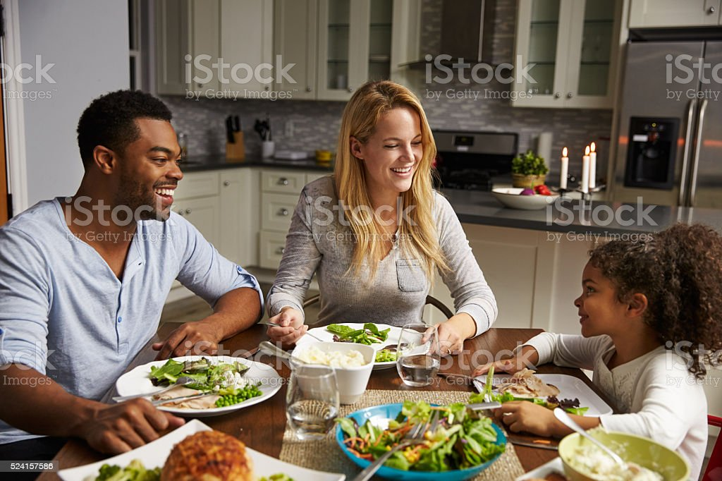 Girl and her mixed race parents dining in their kitchen stock photo