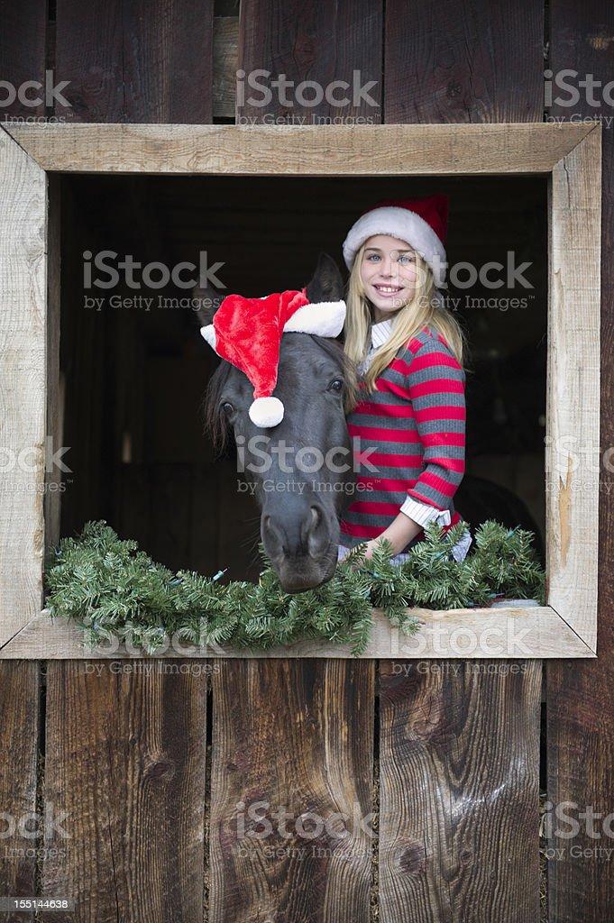 Girl and Horse in Santa Christmas Hats at Barn Window royalty-free stock photo