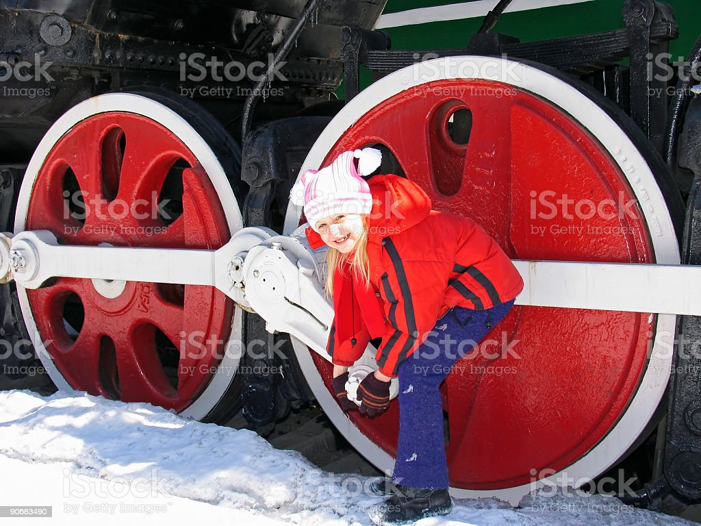 Girl and locomotive wheels royalty-free stock photo