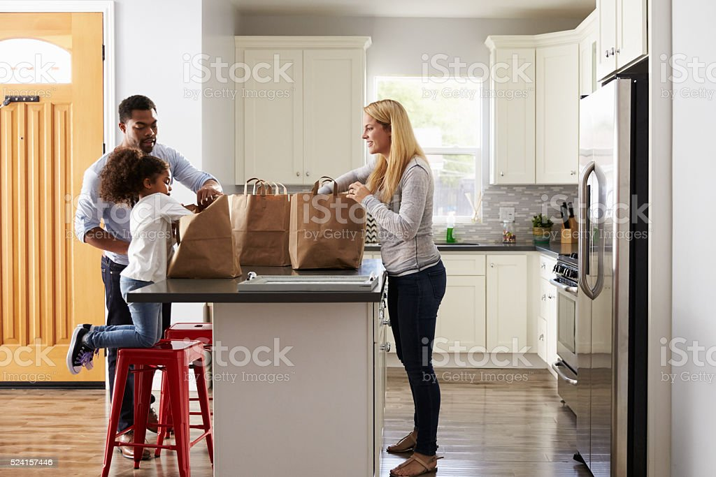 Girl and mixed race parents unpack shopping bags in kitchen stock photo
