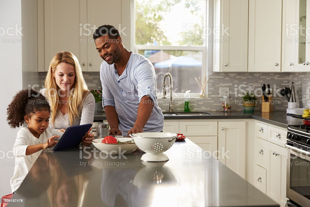 Girl and mixed race parents use tablet computer in kitchen stock photo