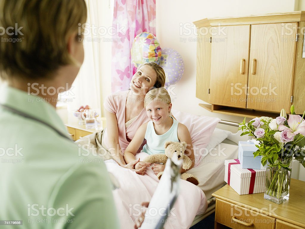 Girl and mother in hospital room with nurse royalty-free stock photo