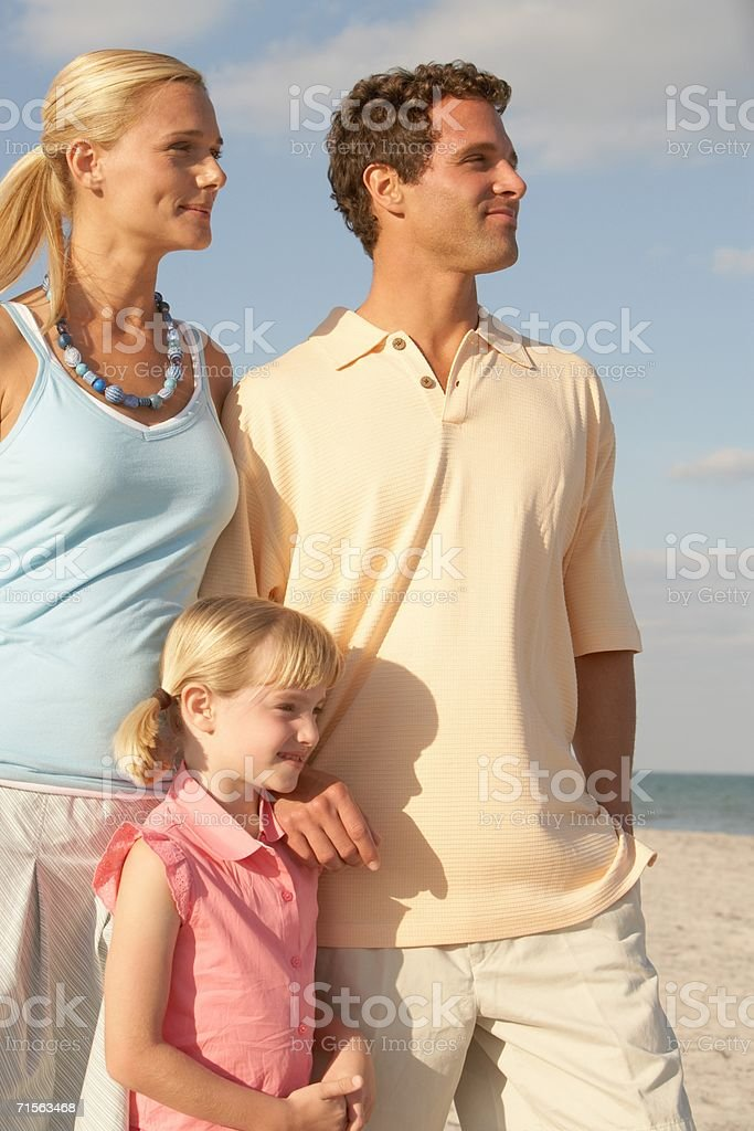 Girl and parents on the beach royalty-free stock photo