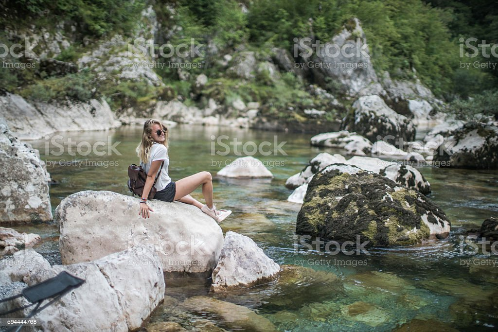Girl and sitting on the rock stock photo