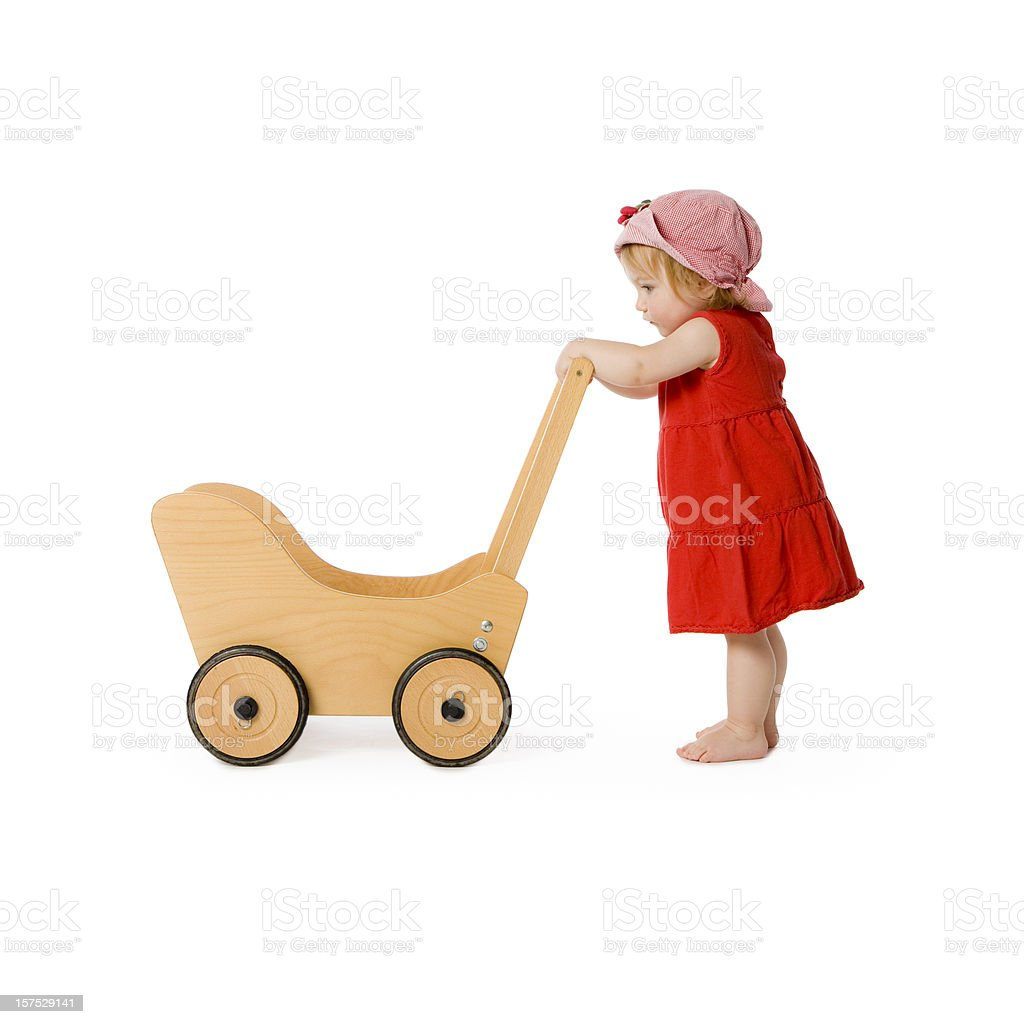 girl and toy wagon. Baby Carriage Toddler Child Pushing royalty-free stock photo