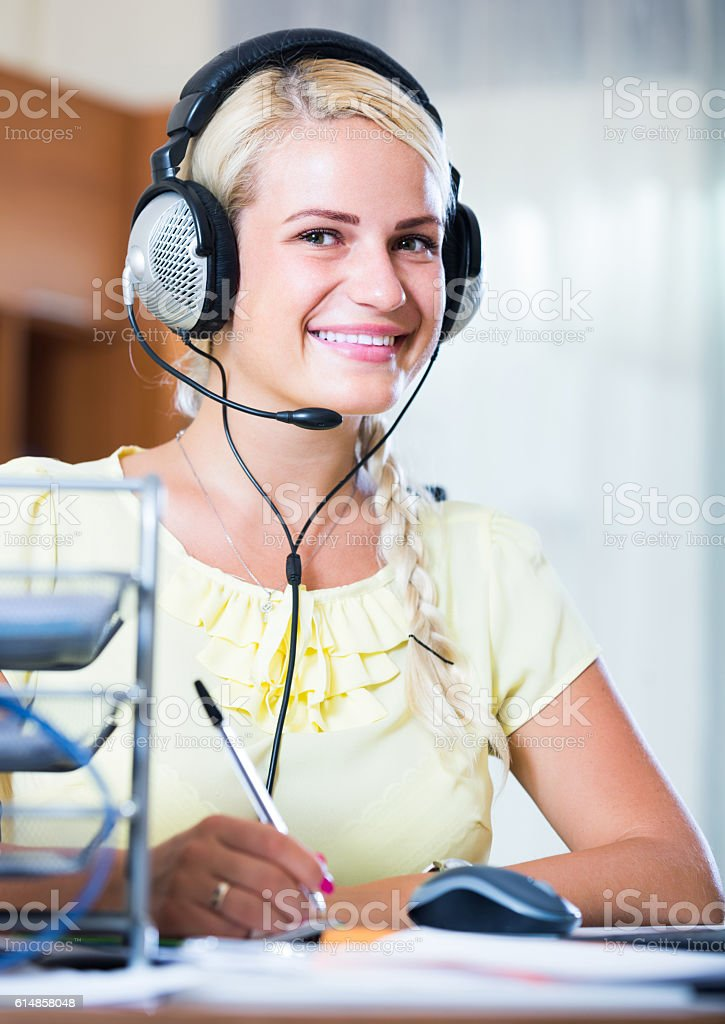 girl answering the call of technical support and smiling stock photo