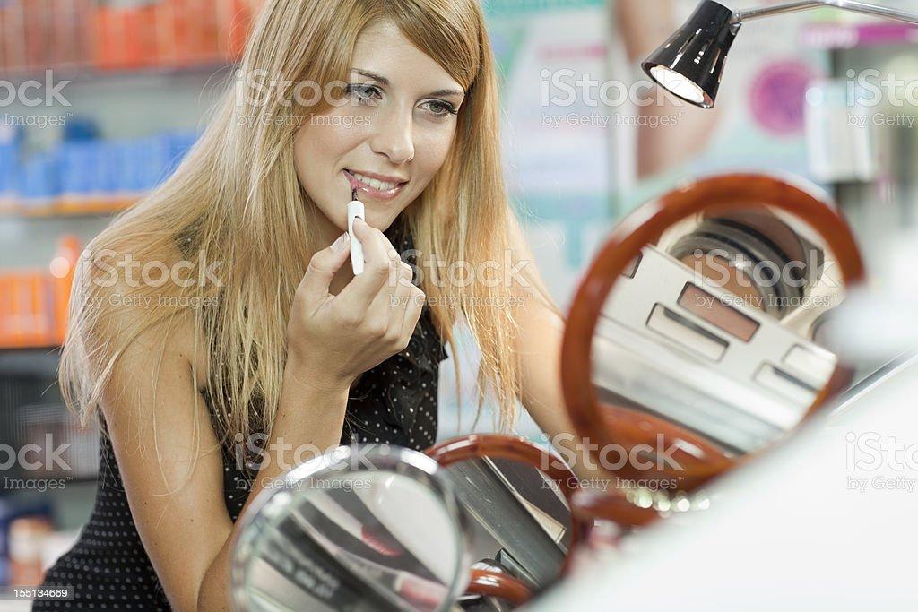 girl applies lipstick on her   lips stock photo