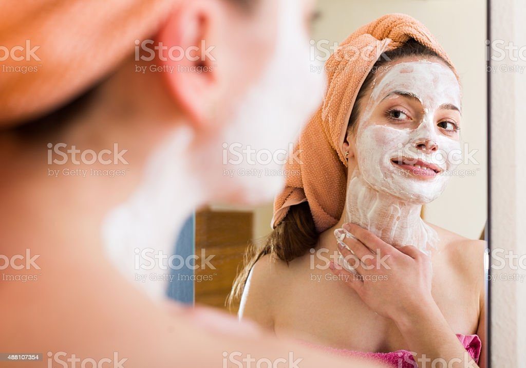 Girl applying cream on skin stock photo