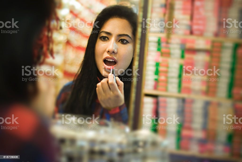 Girl applying lipstick, checking in mirror at cosmetics shop. stock photo