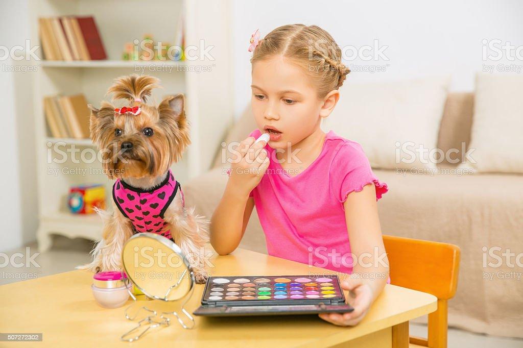 Girl applying make up and terrier beside her stock photo