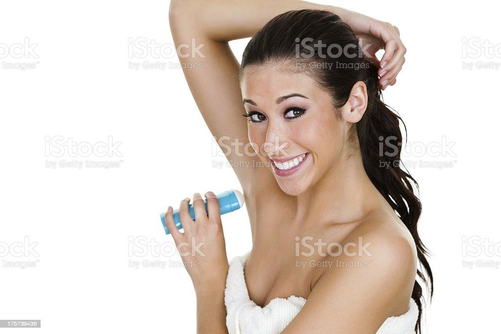 Girl applying underarm deodorant stock photo