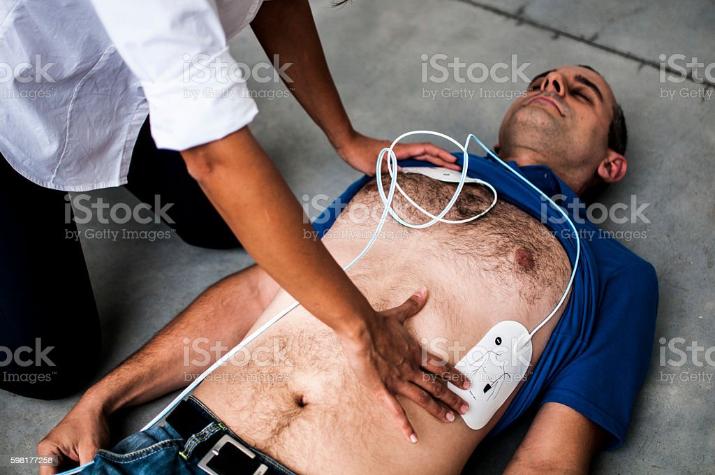 girl assisting an unconscious man after fatal accident stock photo