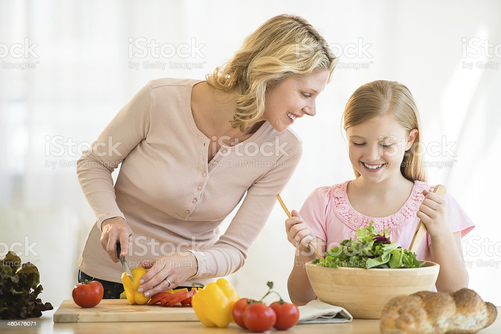 Girl Assisting Mother In Preparing Food At Counter royalty-free stock photo