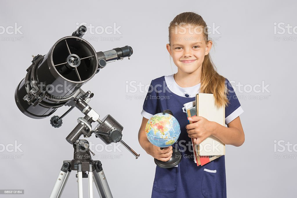 Girl astronomer is a telescope with a globe and stock photo