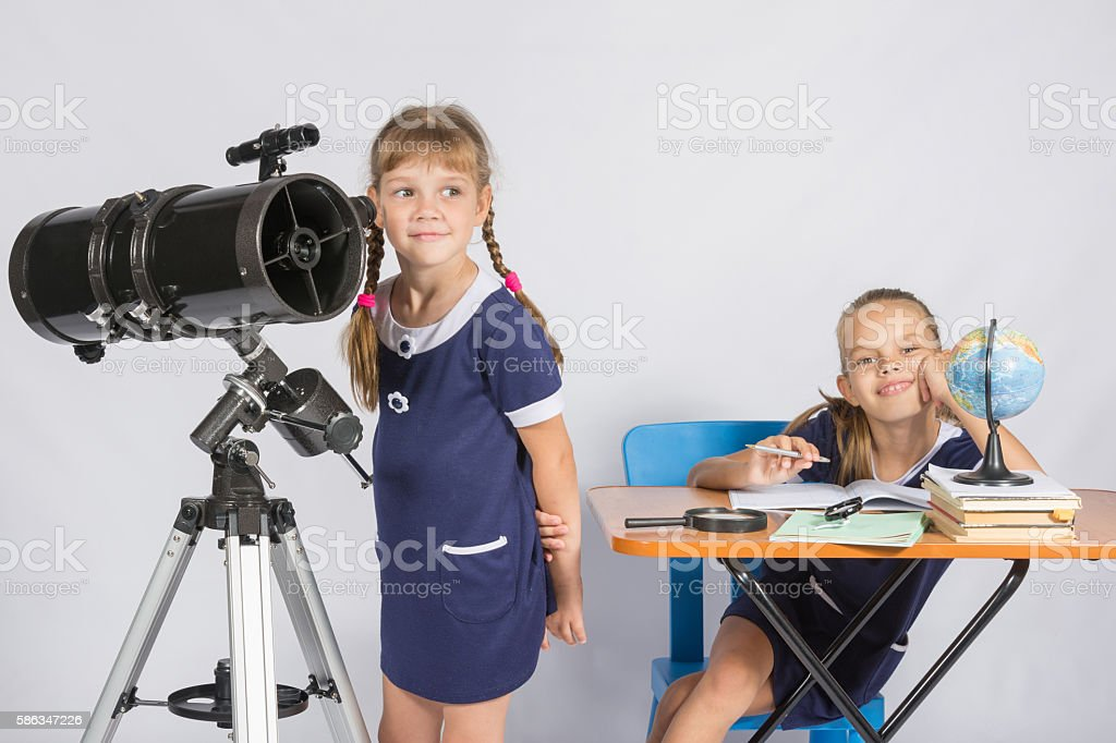 Girl astronomer looks at sky, other girl sitting happily table stock photo