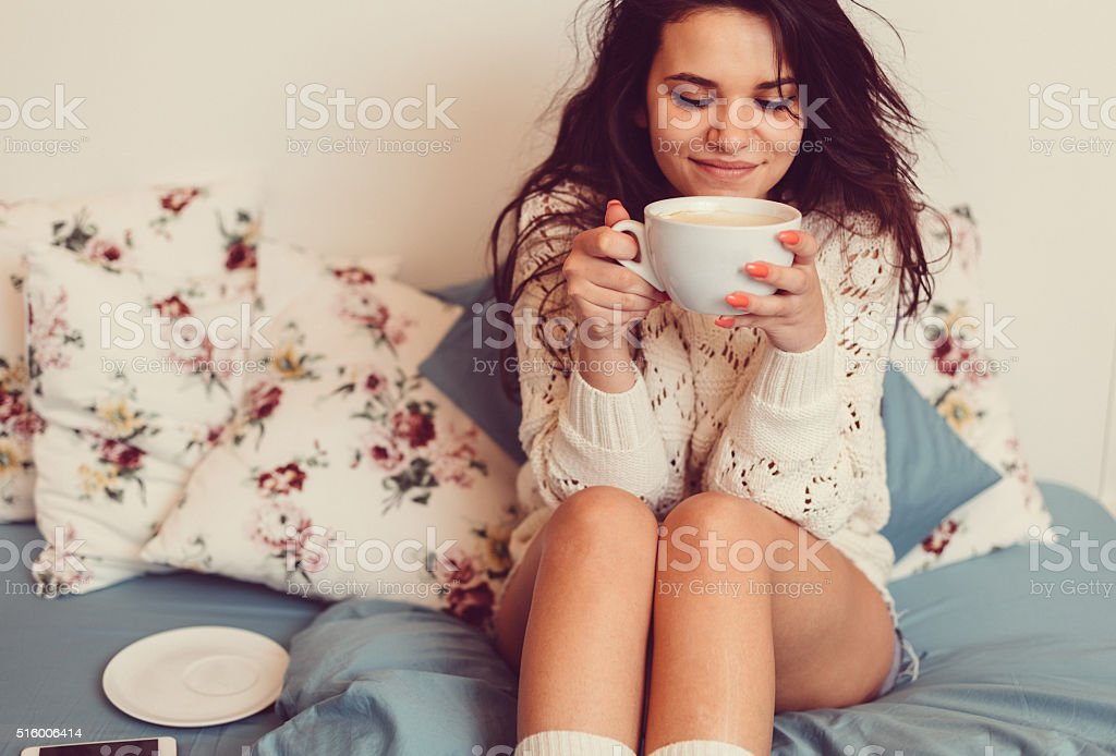 Girl at bed drinking coffee stock photo