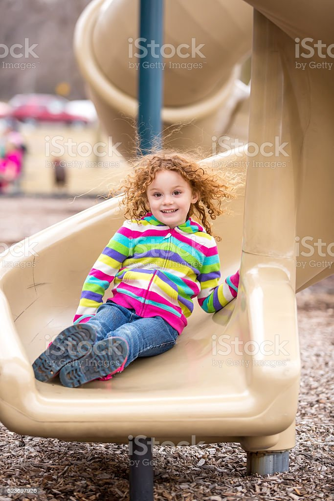 Girl At Bottom of Twisted Slide on Playground stock photo