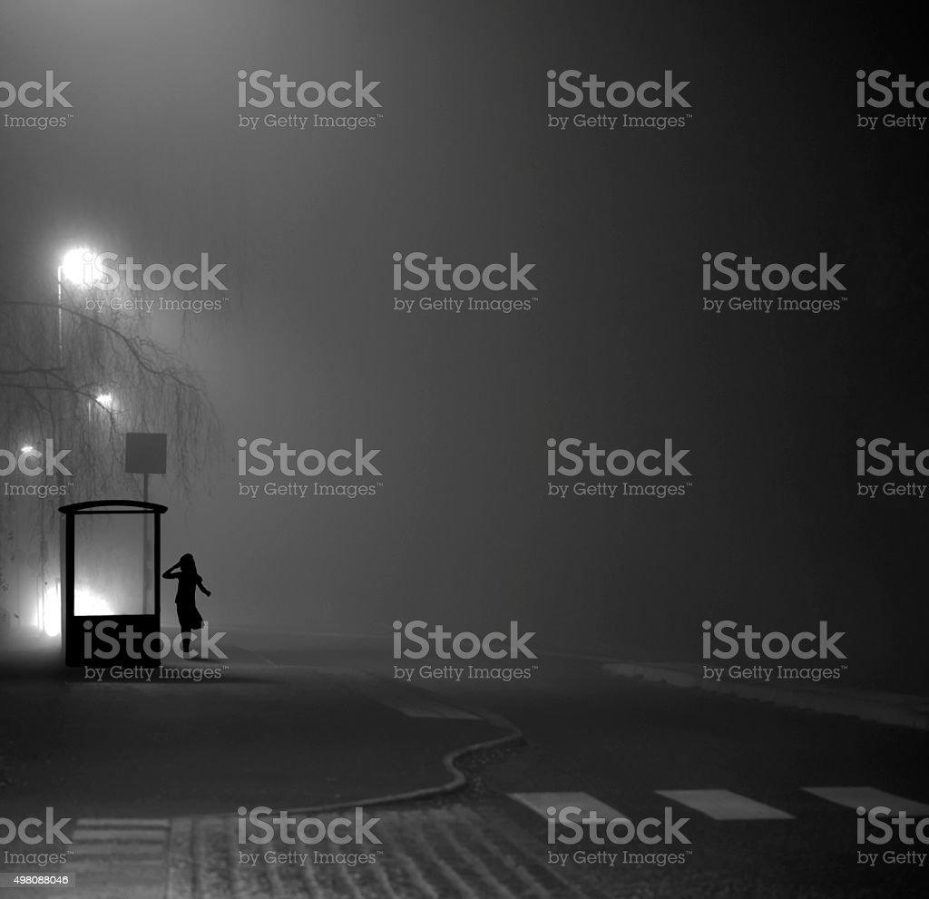 Girl at bus stop at night stock photo