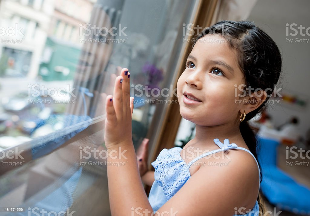 Girl at home looking through a window stock photo