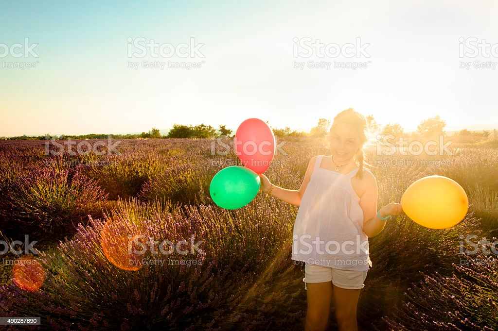 Girl at lavender field holding balloons stock photo