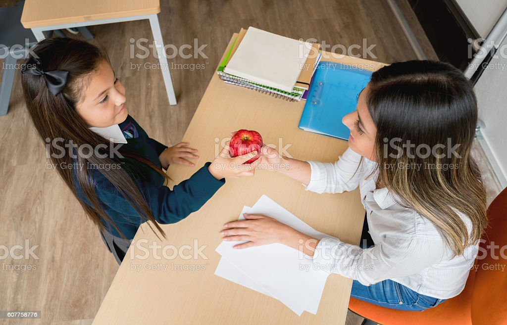 Girl at school giving present to the teacher stock photo