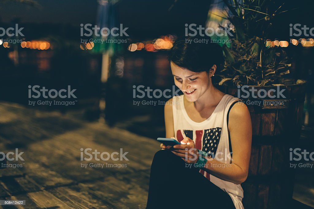 Girl at the beach by night using smartphone stock photo