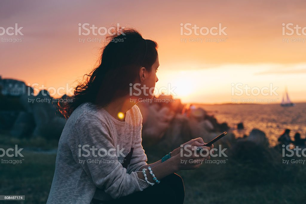 Girl at the beach texting on sunset stock photo