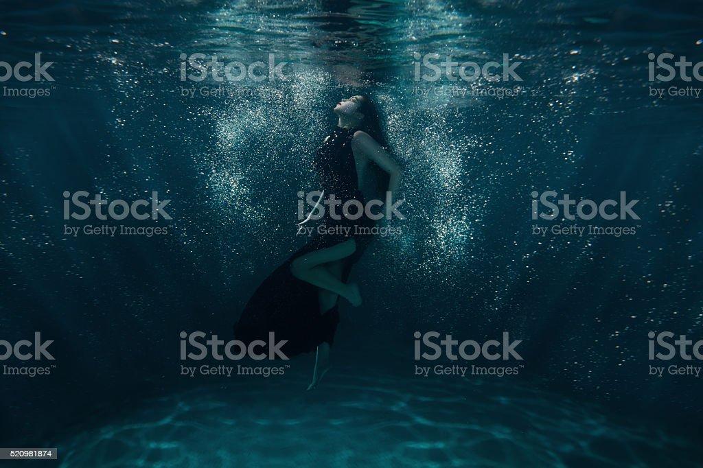 Girl at the bottom among rays. stock photo