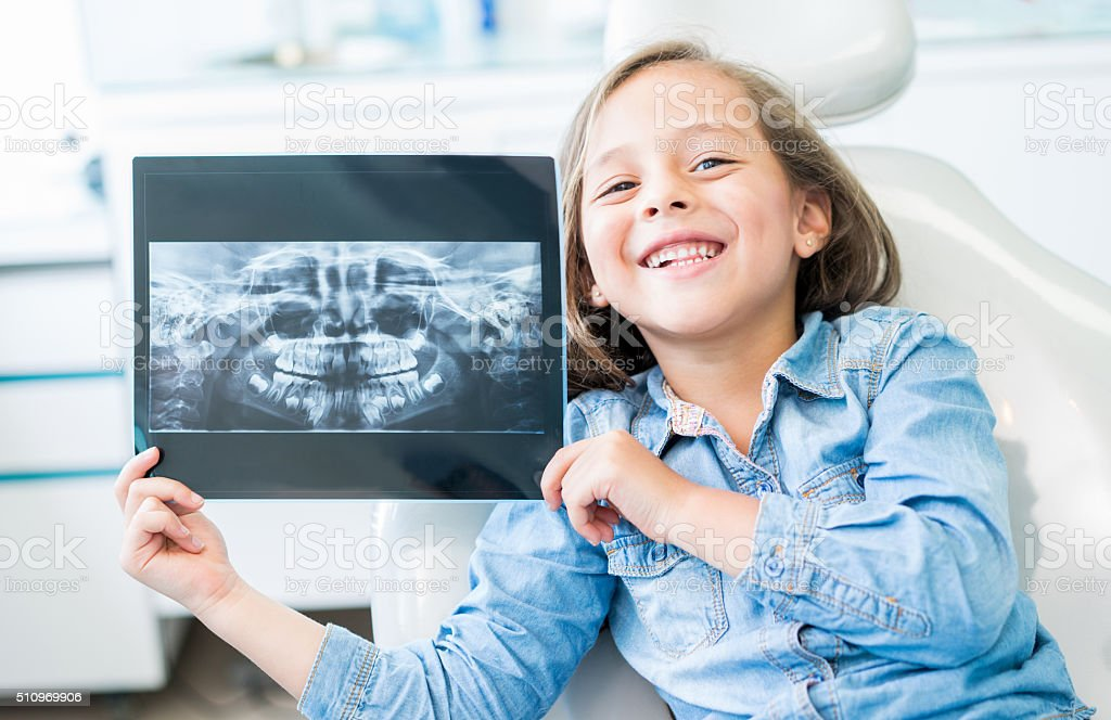Girl at the dentist holding an x-ray stock photo