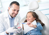Girl at the dentist learning how to brush her teeth