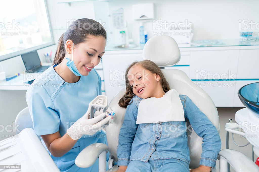 Girl at the dentist learning how to brush her teeth stock photo