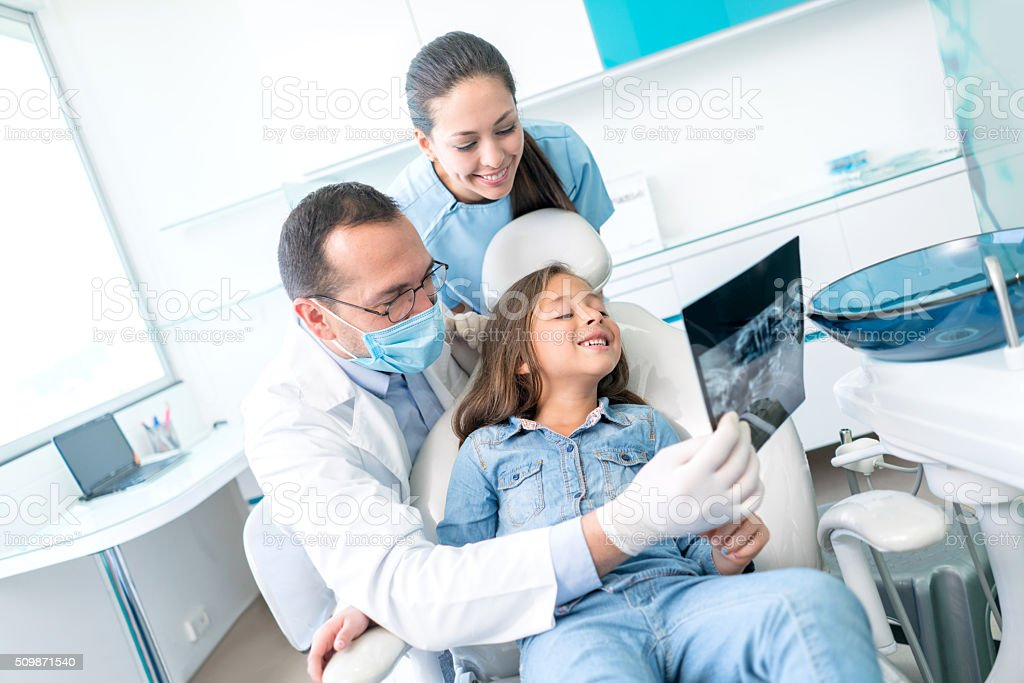 Girl at the dentist looking at an x-ray stock photo