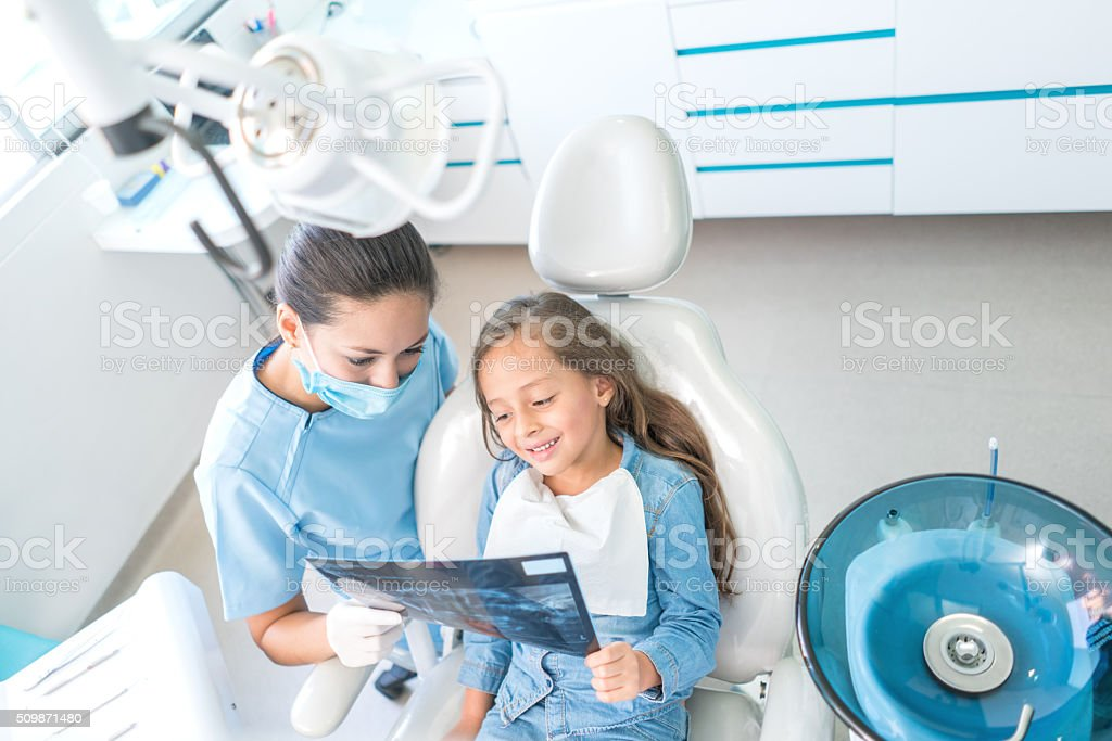 Girl at the dentist looking at her x-ray stock photo