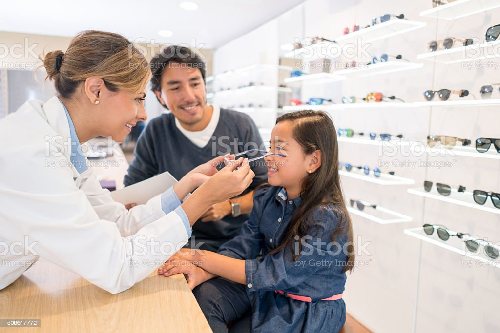 Girl at the optician's shop trying new glasses stock photo