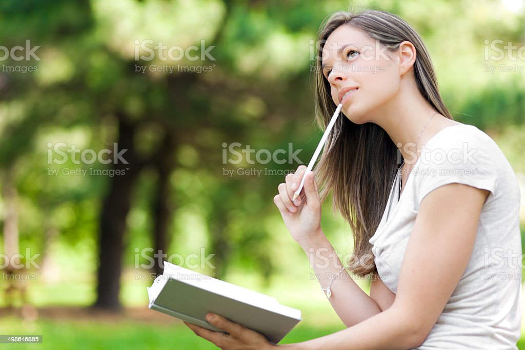Girl at the park writes in her personal diary stock photo