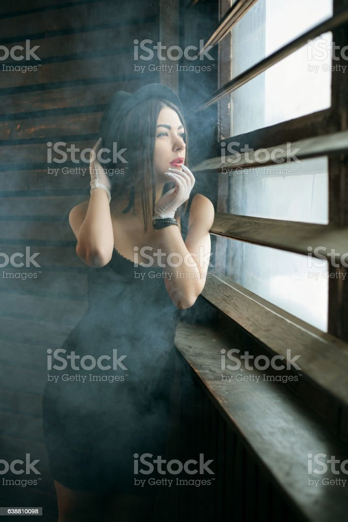 girl at the window in the mist stock photo