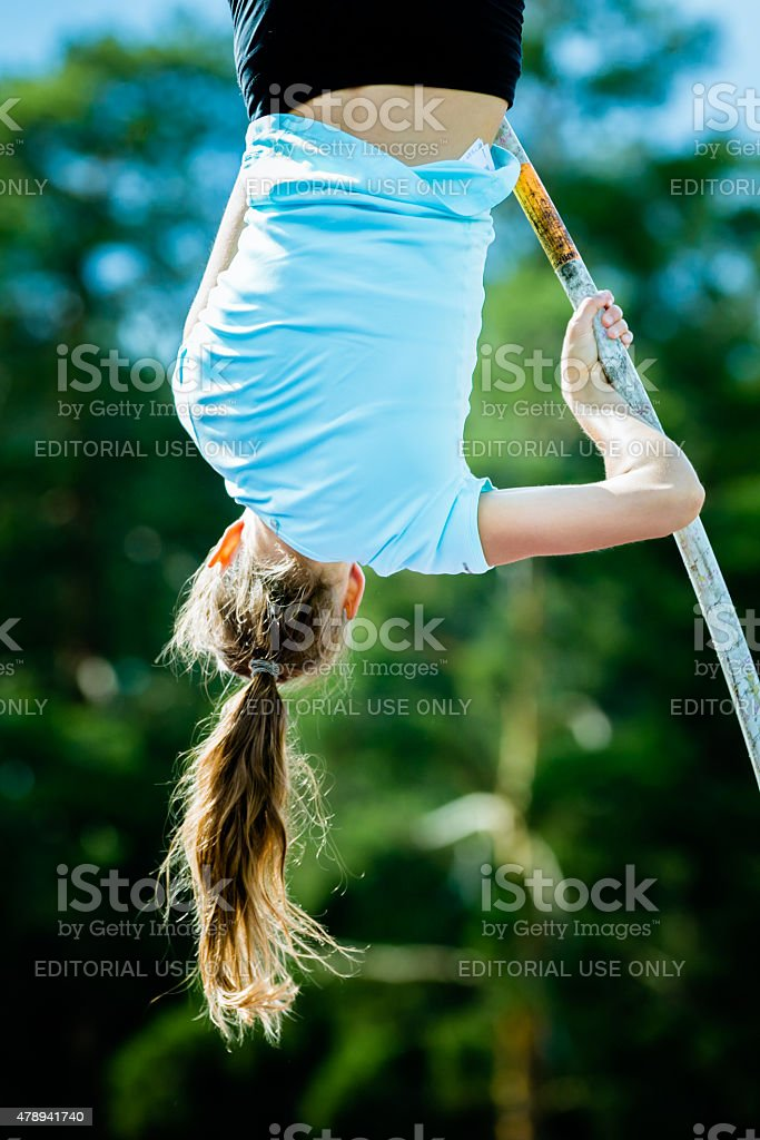 Girl athlete competing in the pole vault stock photo